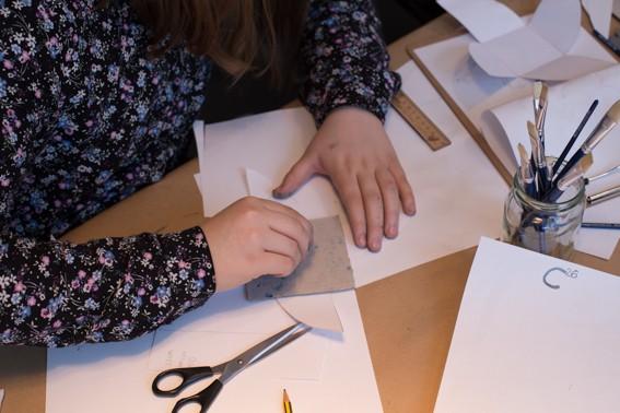 Die Hände einer Person beim Basteln, auf dem Tisch liegen verschiedene Papiere, eine Schere, ein Lineal und ein Glas mit Pinseln